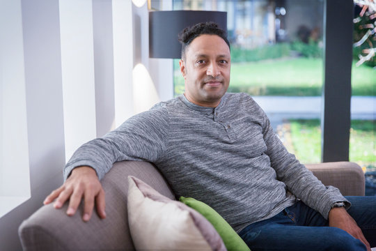Portrait confident man on living room sofa
