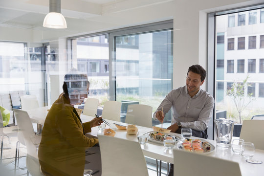 Business people eating sushi lunch in conference room