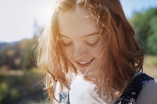 Smiling young woman with freckles looking down