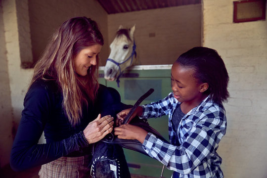Woman helping girl prepare saddle in horse stables