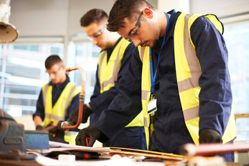 Focused male students in shop class workshop