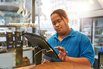 Young woman with Down Syndrome working at cash register in cafe Wall mural