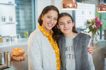 Portrait happy mother and daughter hugging in kitchen