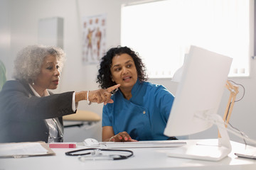 Female doctor and patient using computer in doctors office