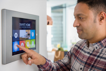 Man setting smart home navigation system alarm at touch screen
