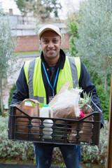 Portrait confident, friendly grocery deliveryman at front stoop