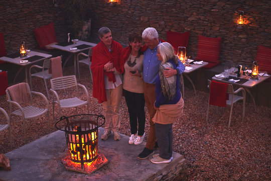 Happy senior friends relaxing at fire pit on hotel patio