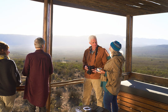 Senior couple with camera and tea on sunny safari lodge balcony