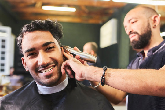 Portrait smiling young man receiving haircut at barbershop