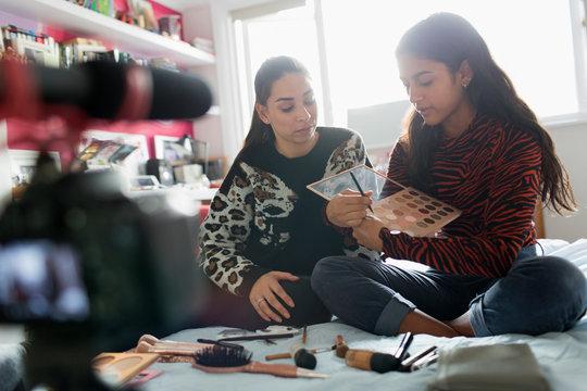 Teenage girls vlogging, demonstrating makeup application on bed