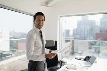 Portrait confident businessman with paperwork in urban office Wall mural