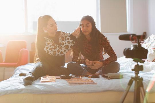 Teenage girls vlogging, demonstrating makeup application in sunny bedroom