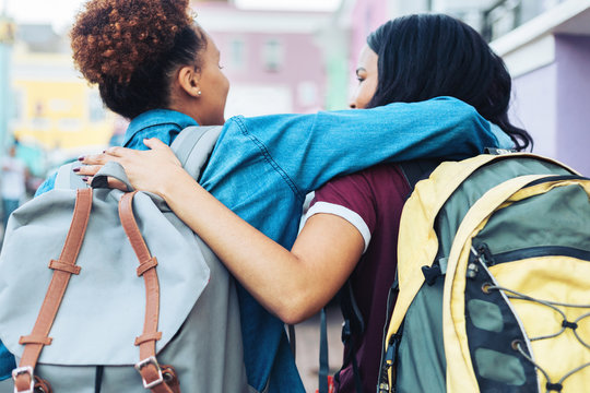 Affectionate young women friends with backpacks hugging