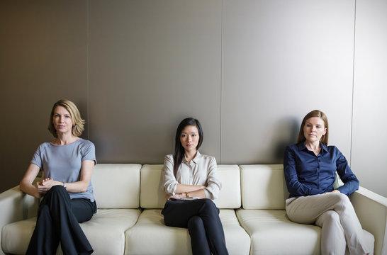 Portrait serious businesswomen waiting on sofa