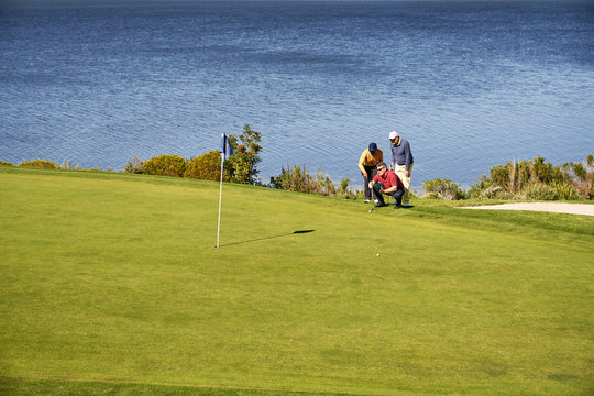 Male golfers planning putt shot at sunny lakeside golf course