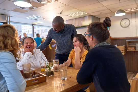 Happy young women with Down Syndrome in cafe with friends