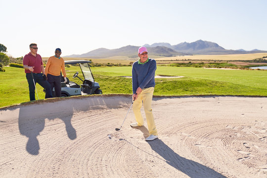 Senior man shooting out of bunker on sunny golf course