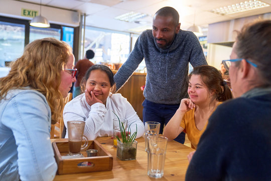 Young women with Down Syndrome talking to friends in cafe