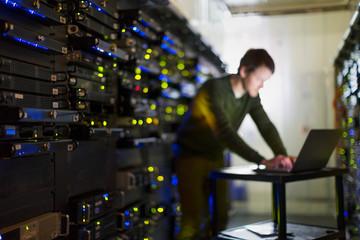 Server room technician working at laptop in corridor