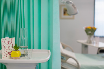 Get Well Soon card and water carafe on tray in vacant hospital room
