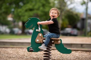 Carefree cute toddler girl riding dinosaur toy at playground
