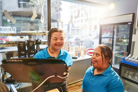 Happy young women with Down Syndrome working in cafe