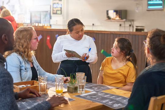 Young female server with Down Syndrome taking order in cafe