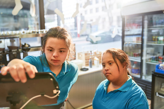 Young women with Down Syndrome working in cafe