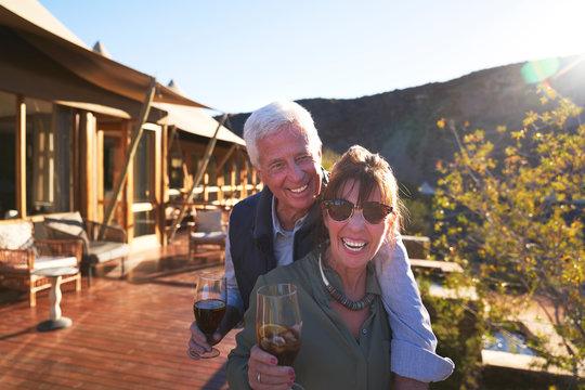 Portrait happy senior couple drinking iced tea on sunny hotel balcony
