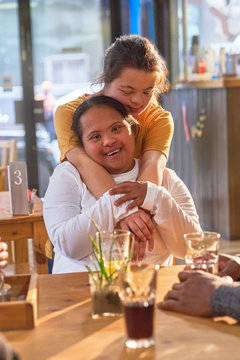 Portrait happy affectionate young women with Down Syndrome in cafe