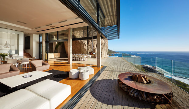 Fire pit and furniture on modern luxury beach house patio with sunny ocean view