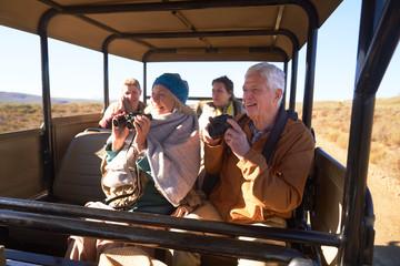 Happy seniors with binoculars and camera on safari in off-road vehicle