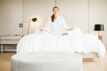 Serene woman in bathrobe meditating in lotus position on bed