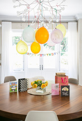Smiley face balloons and Happy Birthday sign hanging over table with cards