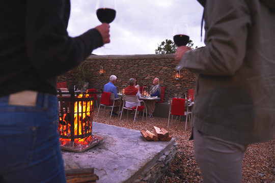 Couple and senior friends dining drinking wine on patio with fire pit