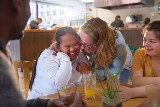 Happy mentor and young women with Down Syndrome laughing in cafe