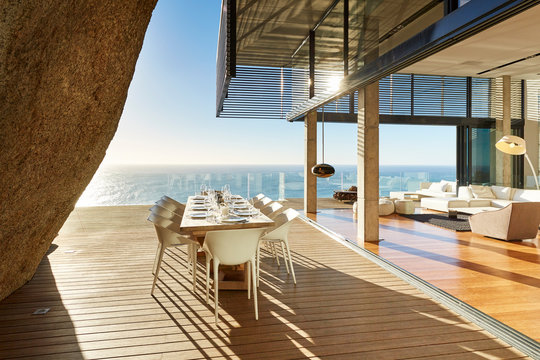 Modern luxury dining table on sunny patio with ocean view