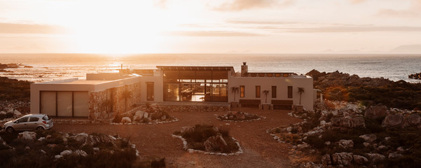 High angle view of luxury home overlooking ocean at sunset