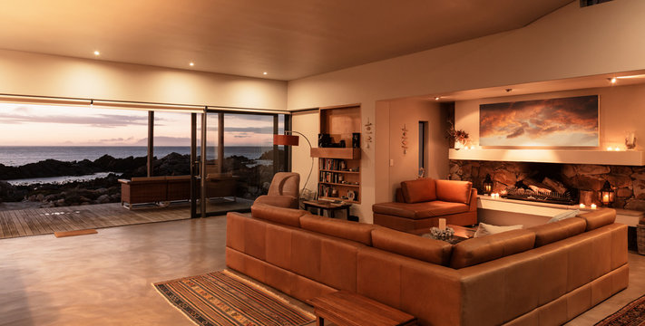 Home showcase interior living room overlooking ocean at sunset