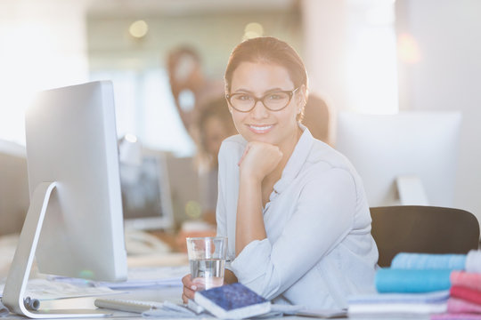 Portrait smiling businesswoman at computer in office