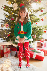 Portrait smiling girl wearing elf costume in front of Christmas tree