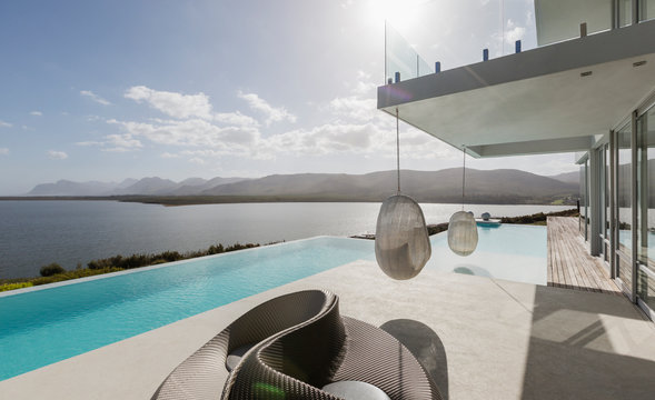 Sunny modern luxury home showcase exterior with infinity pool and ocean view