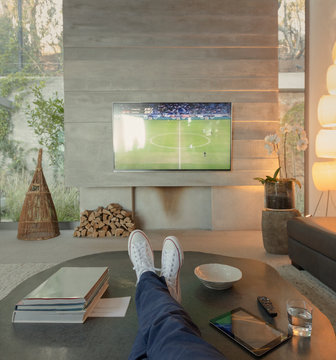 Personal perspective woman watching soccer on TV in living room