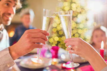 Couple toasting champagne flutes at Christmas dinner