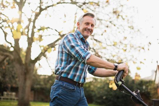 Portrait smiling senior man mowing lawn