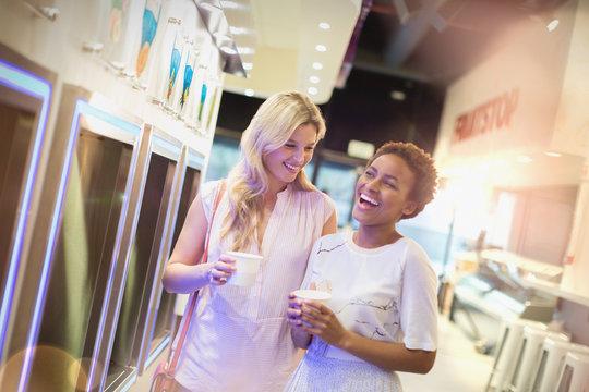 Laughing young lesbian couple enjoying frozen yogurt