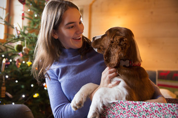 Teenage girl petting dog in Christmas gift box