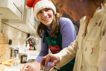 Happy mother and teenage daughter in Christmas Santa hat baking in kitchen