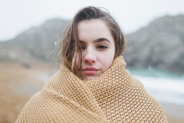 Portrait confident, serious girl with snow in hair wrapped in blanket on winter beach