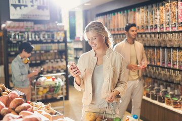 Young woman using cell phone, grocery shopping in market